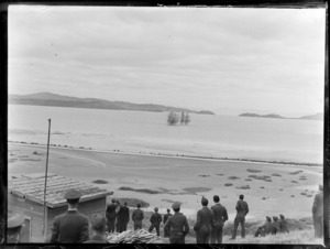 Members of the Royal New Zealand Air Force standing on a hill, watching rockets fire into the sea, Auckland