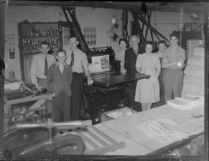 Portrait of Leader Press Group unidentified personnel in their workshop standing beside a printing press, location unknown