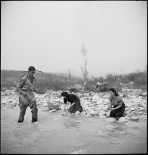 B A Nicholls demonstrates a knapsack sprayer to spray oils on the water at NZ Malarial School, Italy, World War II - Photograph taken by M D Elias