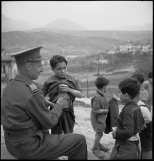 Major H T Knights examines Italian children for symptoms of malaria, Italy, World War II - Photograph taken by M D Elias