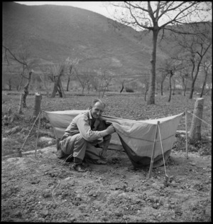 Staff Sergeant R R Rae showing mosquito-proof net to be issued to forward troops of 2 NZ Division in Italy, World War II - Photograph taken by M D Elias