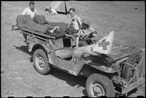 Unloading patients from a stretcher jeep by 6 NZ Field Ambulance personnel in Italy, World War II - Photograph taken by George Bull