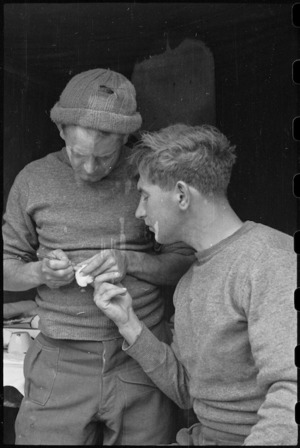 C Purchase dresses a slight cut for L W Feathery at Regimental Aid Post truck in Divisional HQ area, Casale, Italy, World War II - Photograph taken by George Bull