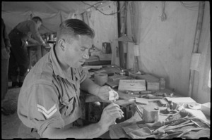 J Franklin waxes up a partial denture at Headquarters of the 1 New Zealand Mobile Dental Unit, Volturno Valley, Italy - Photograph taken by George Bull