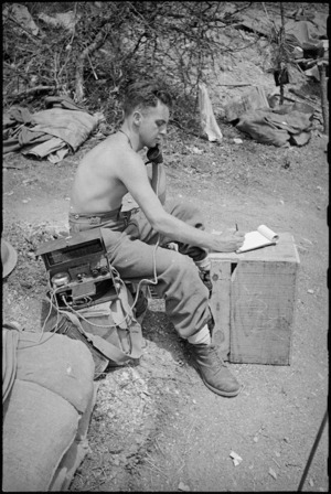 E Dominey at Platoon HQ receives message from Company HQ in forward areas of 8th Army Front, Italy World War II - Photograph taken by George Kaye