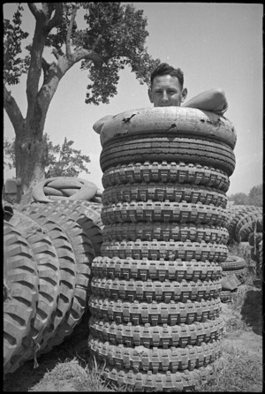 E H Tweedy with tyres for 2 NZ Division vehicles in forward areas of the Cassino Front, Italy, World War II - Photograph taken by George Kaye