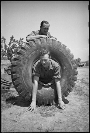 J McLennan and R Gibbs with large sized tyre for 2 NZ Division vehicle, Cassino Front, Italy, World War II - Photograph taken by George Kaye