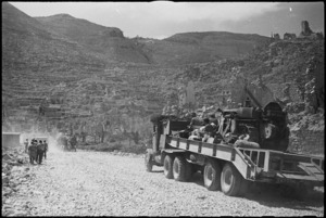 Tank transporter carrying bulldozer moving through the ruins of Cassino, Italy, World War II - Photograph taken by George Kaye