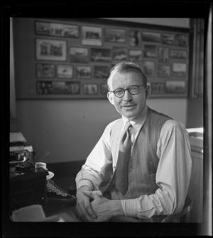 Portrait of J B Claydon of Whites Aviation sitting at his typewriter, Whites Aviation Office, Auckland
