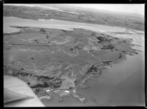 View of the Kellihers' Puketutu Island farm and road access causeway with Mangere and Manukau City beyond, Manukau Harbour, South Auckland