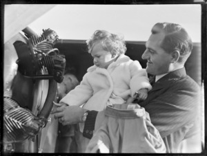 Mr K Davies, holding a small child, at Auckland Aero Club