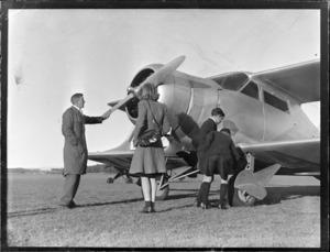 Auckland Aero Club, Mangere, Auckland, showing a group of unidentified people standing in front of a Beechcroft aircraft, checking out the propellor and wheels of the aircraft