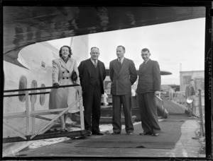 British Oversea's Airways Corporation's Mrs Wallen on the gangway ramp with Messrs G Roberts, [E A R?] and Leo White, standing next to a flying boat aircraft, Mechanics Bay, Auckland