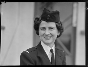 Portrait of Miss B P Morton TEAL Stewardess in uniform outside an unidentified building, [Auckland?]