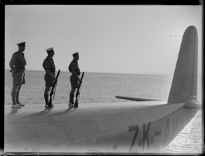 Group portrait of three unidentified RNZN soldiers at attention standing on top of TEAL Short S30 Empire Class flying boat 'Aotearoa' ZK-AMA, Suva, Fiji
