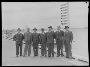 Group portrait of staff of Tasman Empire Airways Ltd, from left; FH Bass, Secretary, TA Barrow, Director, [J?]A Greenland, Director, AE [Dudder?], Chairman, [LJ?] White, Vice-Chairman, W Hudson, Director, G N Roberts, General Manager, standing on a quay, Auckland