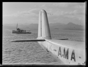 View of harbour, Suva, Fiji, including tail of Tasman Empire Airways Ltd Short Empire flying boat 'Aotearoa' ZK-AMA, and an unidentified boat
