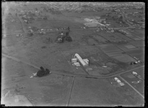 View of the NZ Glue Company factory surrounded by fields with a residential suburb beyond, Onehunga, South Auckland