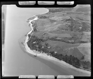 The Hokianga Harbour settlement of Opononi and wharf with State Highway 12 surrounded by farmland, Northland