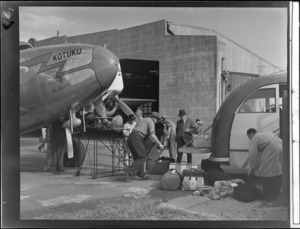 Men unloading luggage from Lockheed Electra aeroplane 'Kotuku', on to a bus, outside Union Airways hangar, Mangere, Auckland