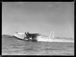 Flying boat 'Aotearoa' ZK-AMA, of Tasman Empire Airways, taxiing across harbour, location unidentified
