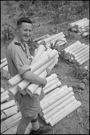 S Mayne busy sorting out the many maps necessary during rapid advance of 2 NZ Division in Italy, World War II - Photograph taken by George Kaye