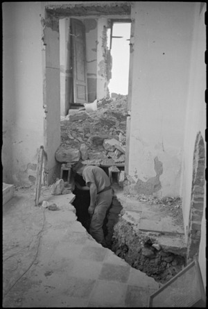 New Zealander investigates German trench in schoolroom at Orsogna, Italy, World War II - Photograph taken by George Kaye