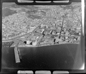 Wellington City southern wharf area with docked ships (now the Overseas Terminal) and State Coal factory, with the suburbs of Mt Victoria and Te Aro with the Dominion Museum on Buckle Street beyond