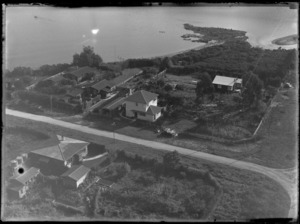 View of local houses on the bank of an unidentified lake or river, Rotorua District