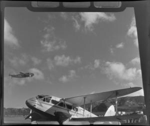 A grounded De Havilland Dominie 'Tawaka' airplane and a Lochead Lodestar in flight, NZNAC (New Zealand National Airways Corporation) [Wellington?]