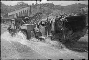 New Zealand breakdown truck towing vehicle over deviation alongside demolished bridge over Pisa River, Italy, World War II - Photograph taken by George Kaye