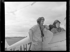 Mr K Robinson and Miss Kelsey, both wearing aviator helmets, with a de Havilland Tiger Moth aeroplane ZK-AHZ, probably at Auckland Aero Club, Mangere, Auckland