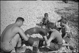 C L Carpenter repairs a tube in the dried up Pisa River bed near Florence, Italy, World War II - Photograph taken by George Kaye