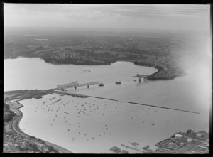 Auckland Harbour Bridge under construction, including Westhaven Marina and Northcote in the distance