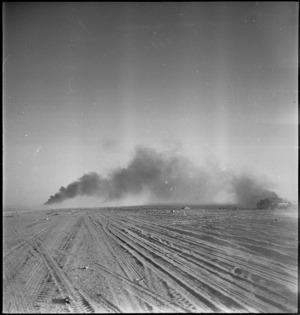 Smoke from burning Italian tanks drifts across 8th Army vehicle tracks at Wadi ZemZem, Libya - Photograph taken by H Paton