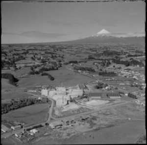 View of an unidentified large factory and railway station with farmland and Mount Taranaki beyond, New Plymouth, Taranaki Region