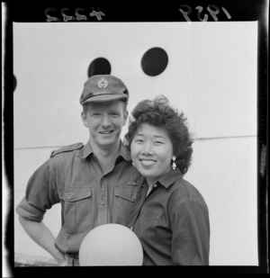 Malayan bride Nancy with her husband Private Laurie McGifford, on Glasgow Wharf, Wellington, after the return of the New Zealand Army from Malaya