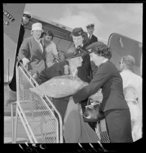 Mrs J Wahren, who is 100 years old, is leaving the aircraft after her flight and being handed flowers from an air stewardess