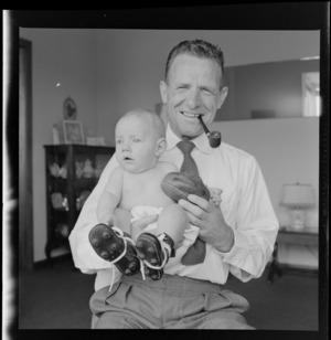 Neill McGregor holding miniature rugby ball and his baby grandson, Neill Thomas McGregor wearing small sized rugby boots