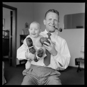Neill McGregor holding miniature rugby ball and his baby grandson Neill Thomas McGregor wearing small sized rugby boots