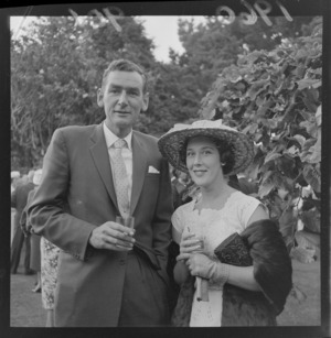 Garden party at Homewood with an unidentified couple in front of trees, Karori, Wellington