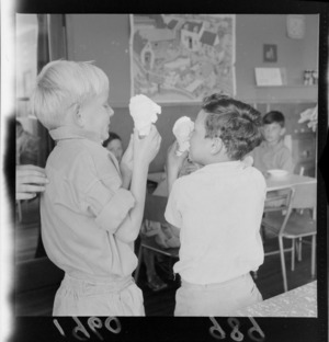 Levin Training Farm for handicapped children with two unidentified children eating ice-creams in cones within a classroom, North Wellington Region