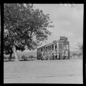 Levin Training Farm for handicapped children with unidentified boys in front of an old Wellington Oriental Bay tram by a tree, North Wellington Region