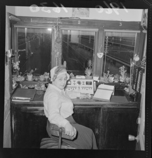 Mrs M Bowden in the Wellington Railway Station announcing box, with small pots of flowers around the office