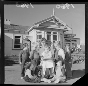 Young children gathered around unidentified woman having a story read to them, Anglican Children's Home, Messines Road, Karori, Wellington