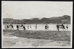 Teams of men running with reels during opening day event, Lyall Bay beach, Wellington