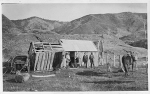 Trampers George Moir and Cyril Woods with two deer stalkers outside Bassett's Hut, Waiohine Valley, Tararua Ranges
