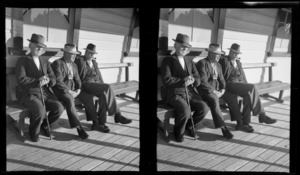 Portrait of three unidentified elderly men sitting outside an unknown wooden building location, South Island