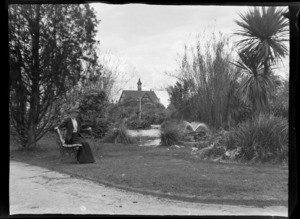 Unidentified woman sitting on park bench next to pond with the Bath House in the background, Government Gardens, Rotorua