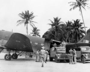 Military trucks alongside a Dakota DC-3 aircraft, Espiritu Santo, Vanuatu , during World War II